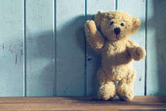 Teddy bear stands in front of a blue wall Royalty Free Stock Images