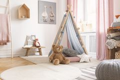 Teddy and star pillow in front of tent in child`s room interior with pouf and poster. Real photo