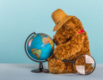 Teddy bear with straw hat, globe and magnifier Royalty Free Stock Image