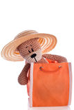 Teddy bear with sun hat in an orange bag Royalty Free Stock Photos