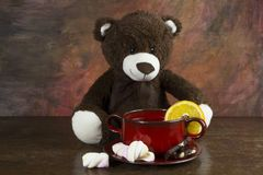 Teddy bear with tea mug on table. Teddy bear with tea mug and donut on wooden table against abstract colorful background stock images