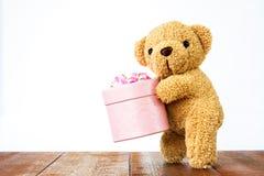 Teddy Bear tenant le boîte-cadeau sur le bois Photo stock