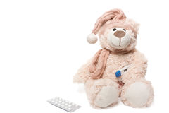Teddy bear with a thermometer and pills Stock Image