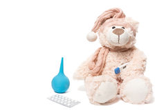 Teddy bear with a thermometer and pills Stock Photos