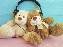 Teddy bear toy headphones listening on wooden background stock photos