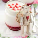 Teddy Bear Toy Leaning over a Jar of Yoghurt with Raspberry Jam Stock Image