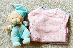 Baby clothes. Teddy bear toy near a Baby clothes on a baby `s bed stock photo