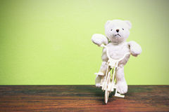 Teddy Bear toy Riding  bicycle on old wood  and green wall backg Royalty Free Stock Photography