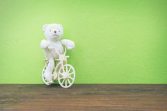 Teddy Bear toy Riding  bicycle on old wood  and green wall backg Stock Photo