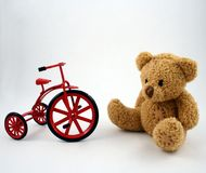 Teddy Bear and Tricycle. A teddy bear and a cast iron toy tricycle stock photo