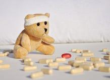 Teddy Bear triste, doente entre comprimidos Imagem de Stock Royalty Free
