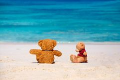 Teddy Bear trying to reconcile with his friend. Two teddy Bear sitting on the beach with blue sea and sky background. Concept about guilty and sorry Stock Photo