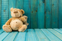 Teddy bear on turquoise wooden background. Stock Photo