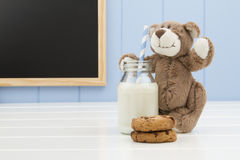 A teddy bear, two chocolate chip cookies and a school milk bottle with a straw Stock Image