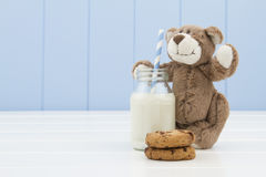A teddy bear, two chocolate chip cookies and a school milk bottle with a straw Royalty Free Stock Photo
