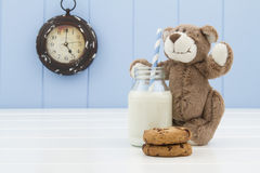A teddy bear, two chocolate chip cookies and a school milk bottle with a straw Royalty Free Stock Photography