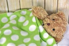 Teddy bear under polka dot blanket Royalty Free Stock Image