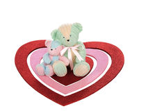 Teddy Bear Valentine. An isolated angled closeup studio view of two teddy bears sitting on three various shaped glitter hearts Stock Image