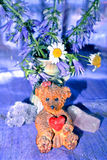 Teddy bear and vase with violet flowers and gemstones Stock Photos