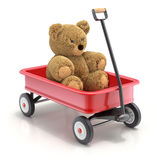 Teddy bear in the vintage child`s toy mini wagon Stock Photo