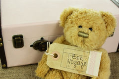 Teddy Bear with vintage suitcase and bon voyage luggage tag Stock Image