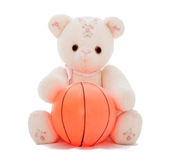 Teddy bear wants to play ball. Flower teddy bear holding out a basketball, isolated on white.  Part of series featuring the same bear Royalty Free Stock Images