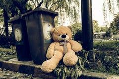 The teddy-bear was throw away sitting beyside the garbage trash. Teddy-bear was throw away sitting beside the garbage trash stock photo