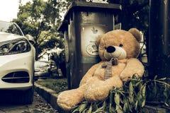 The teddy-bear was throw away sitting beside the garbage trash. A teddy-bear was throw away sitting beside the garbage trash stock photo