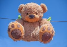 Teddy bear washing and drying. Sky sunshine clothespins toy brown wet roof rope royalty free stock photography