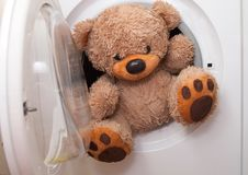 Teddy bear washing and drying. Sky sunshine clothespins toy brown wet roof rope washing machine white royalty free stock photos