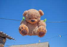 Teddy bear washing and drying. Sky sunshine clothespins toy brown wet roof rope stock image