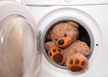 Teddy bear washing and drying. Sky sunshine clothespins toy brown wet roof rope washing machine white stock image