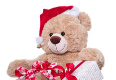 Teddy bear wearing Christmas hat with gifts isolated on white ba Stock Photo