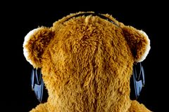 Toy Teddy Bear From Rear With Large Headphones on Black. Teddy Bear wearing large headphones from rear on a black background stock image