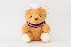 Teddy bear wearing a nurse hat. Teddy bear wearing a nurse hat on a white background stock photo