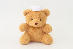 Teddy bear wearing a nurse hat. Teddy bear wearing a nurse hat on a white background royalty free stock image