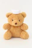 Teddy bear wearing a nurse hat. Teddy bear wearing a nurse hat on a white background royalty free stock images