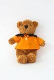 Teddy bear wearing an orange. Royalty Free Stock Image