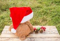 Teddy bear wearing santa claus hats on wooden table Stock Photos