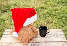 Teddy bear wearing santa claus hats on wooden table Stock Photo