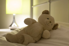 Teddy bear on white bed Stock Images