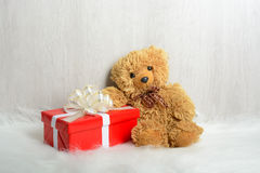 Teddy bear on a white carpet with gifts Stock Photo