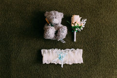 Teddy bear  with white garter and orange buttonhole on the green background Stock Images