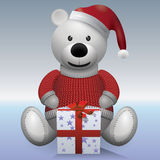 Teddy bear white in red sweater and red hat with present.  Stock Image