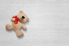 Teddy bear on white wooden deskt with free space for text Stock Photos