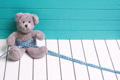 Teddy bear on a white wooden floor  blue-green background with centimeter. Diet and weight loss in children Stock Image