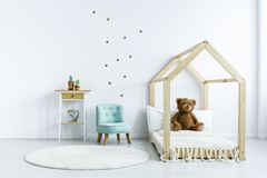 Teddy bear on wooden bed next to blue chair in white kid`s bedro stock photo