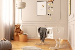 Bear on wooden stool in fashionable nursery with white wooden cradle with grey blanket. Teddy bear on wooden stool in fashionable nursery with white wooden royalty free stock photography