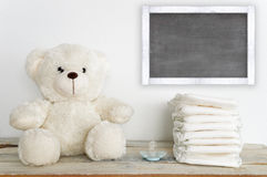 A teddy bear on a wooden table next to a pacifier and some diapers. Stock Photos