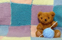 Teddy bear with a woolen ball on a knitted background. Brown teddy bear, Teddy bear with a woolen ball on a knitted background, knitted squares, knitted plaid of stock photos